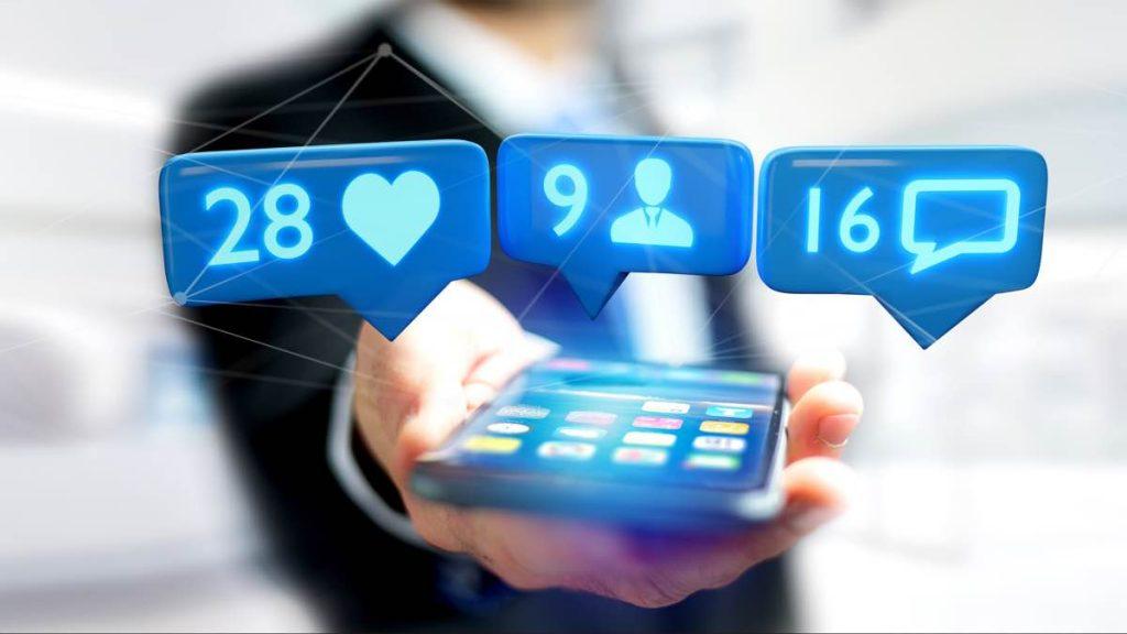 Hombre usando un teléfono que muestra número de likes, seguidores y comentarios de Instagram