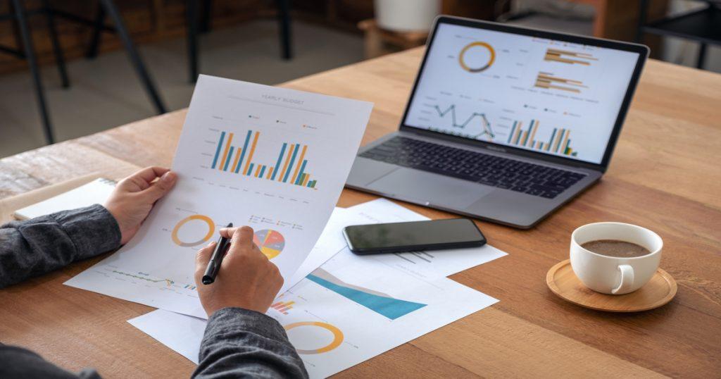 Un hombre revisando gráficas y métricas de su negocio sobre un escritorio