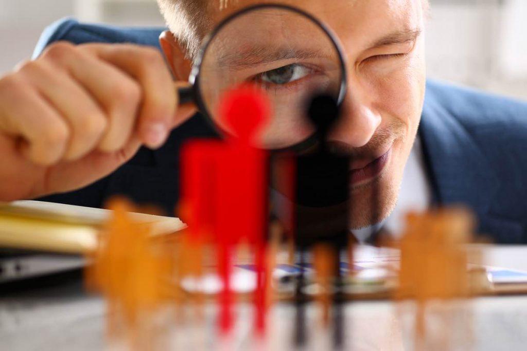 Hombre examinando con lupa dos perfiles para una oferta de empleo