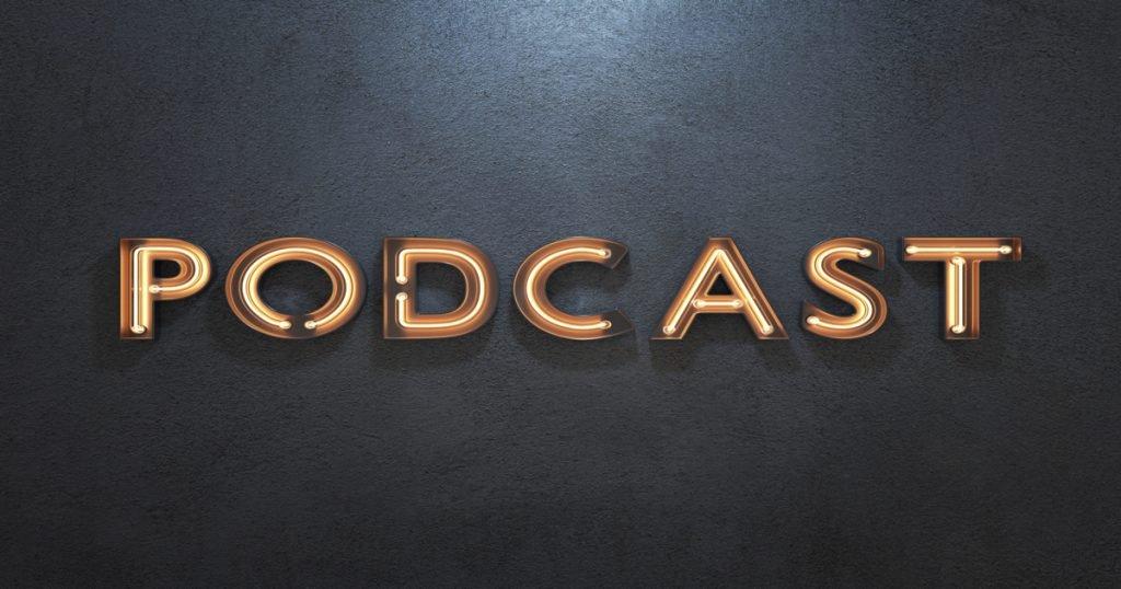 """Letrero luminoso sobre fondo negro, donde se puede leer la palabra """"podcast"""""""