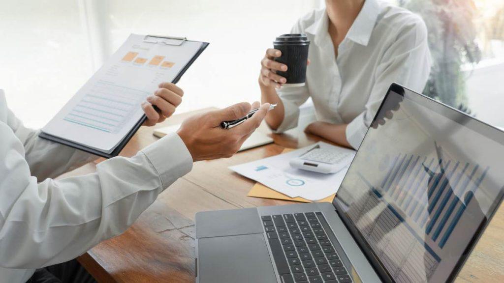 Compañeros de trabajo analizando estadísticas y gráficas de la empresa