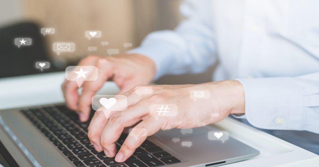 Manos de hombre escribiendo sobre el teclado de un ordenador portátil.