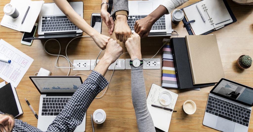 Cinco personas juntando sus puños en símbolo de unión sobre un escritorio.