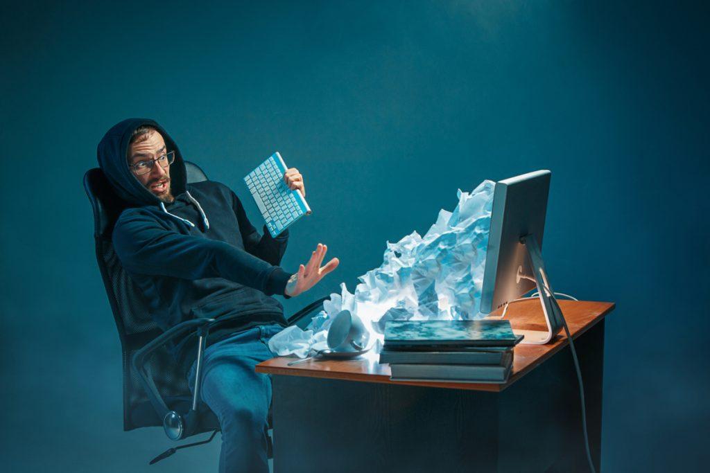 Hombre frente al ordenador estresado por recibir muchos emails