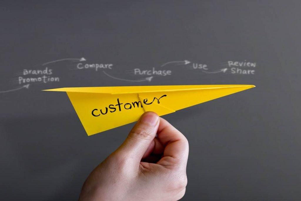 """Mano sujetando avión de papel de color amarillo con la palabra """"customer"""" escrita"""