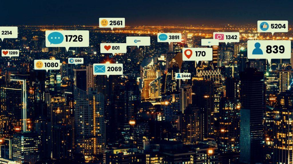 Ciudad con avisos de notificaciones de redes sociales saliendo de los edificios
