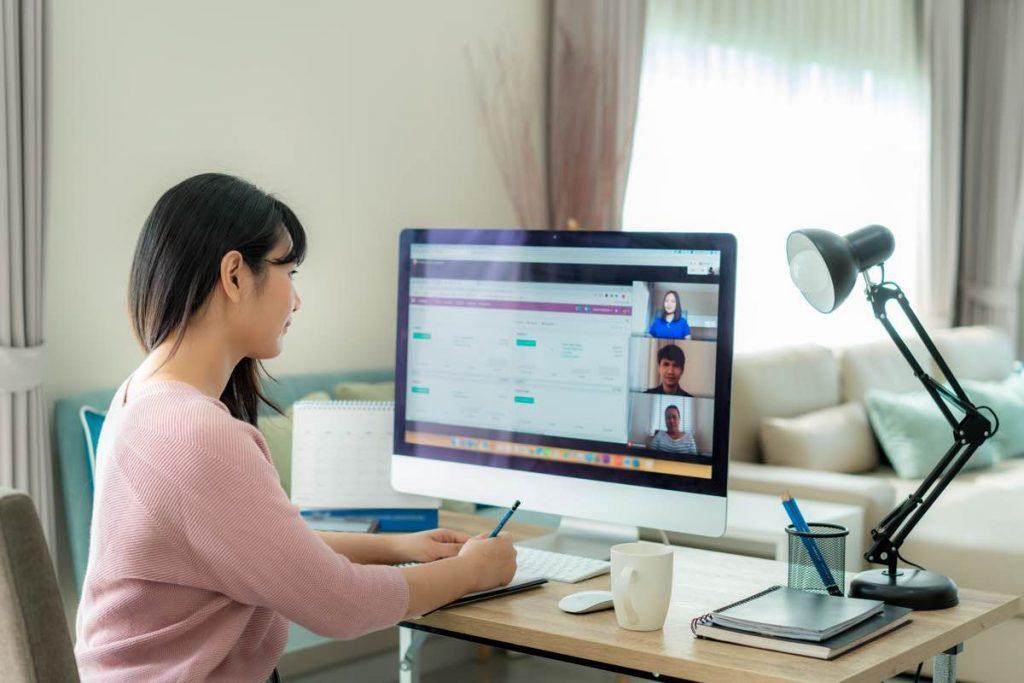 Mujer asistiendo desde casa a una videoconferencia con sus compañeros de trabajo a través del ordenador