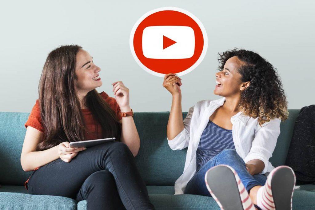 Dos chicas sentadas en un sofá y una de ellas sujeta un cartel con el logotipo de youtube