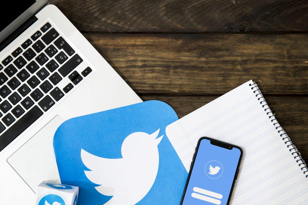Ordenador portátil y teléfono móvil con el logotipo de Twitter en la pantalla