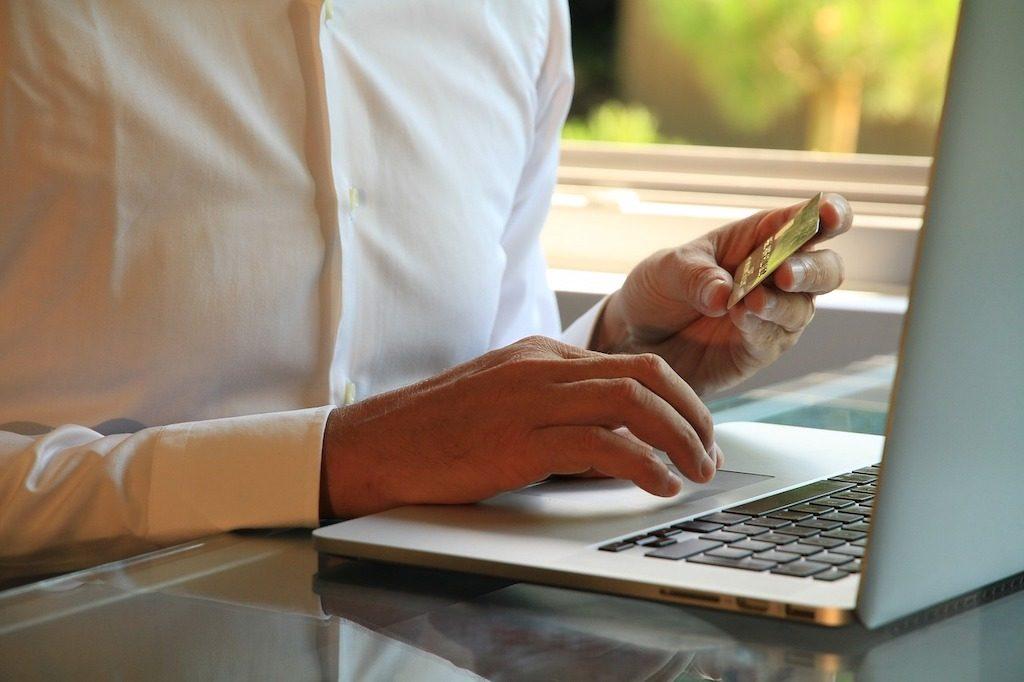 foto de un hombre sujetando una tarjeta de crédito de lante de un ordenador