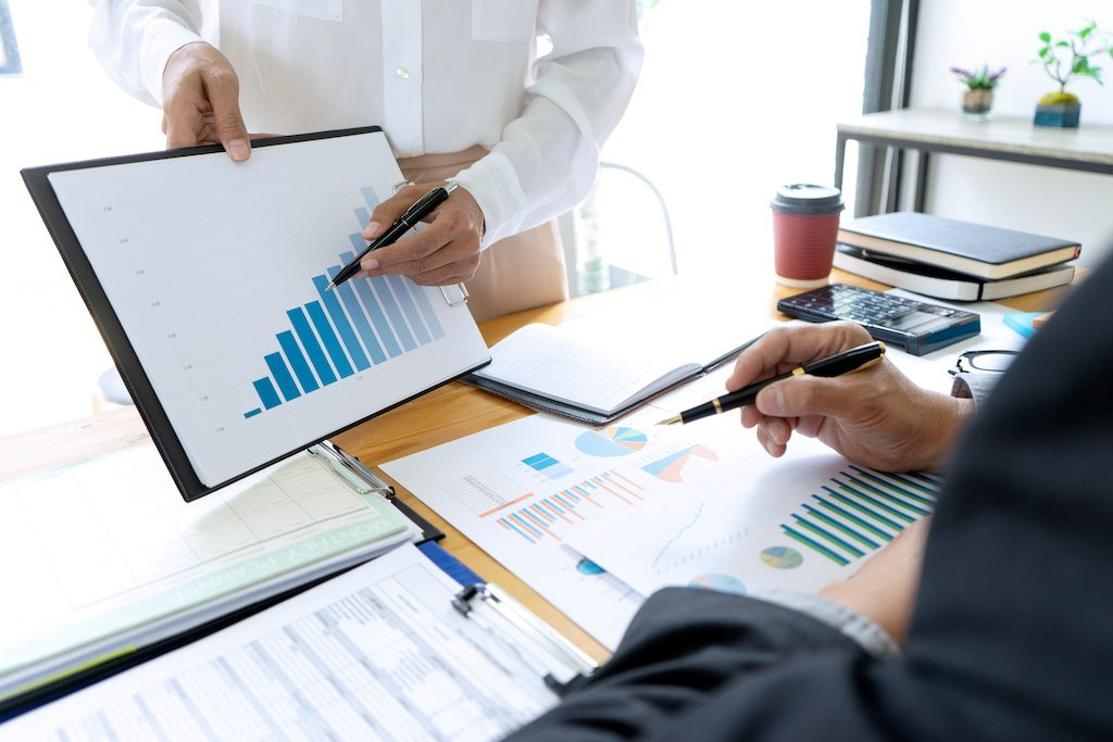 foto de una oficina y varias personas analizando un estudio de mercado