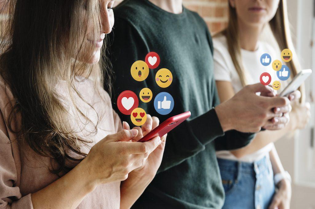 personal utilizando el teléfono móvil y aparecen emojis