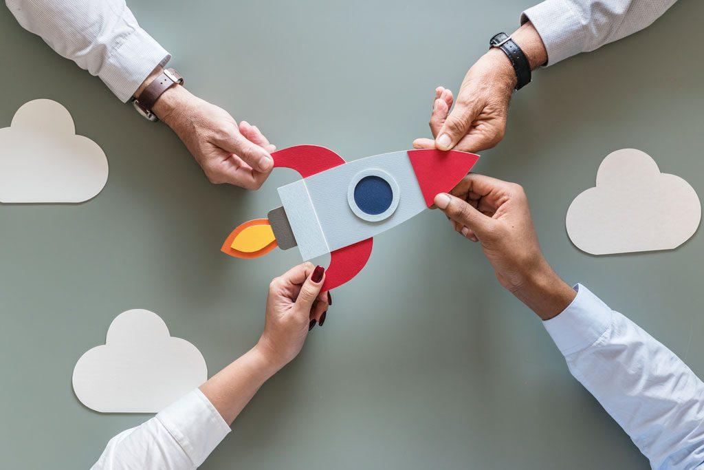 foto de los brazos de cuatro emprendedores sujetando un cohete