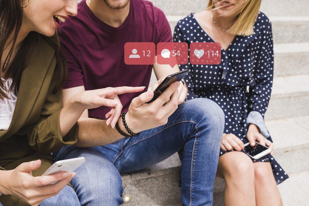 chicos sentados en un escalón mirando un móvil con redes sociales