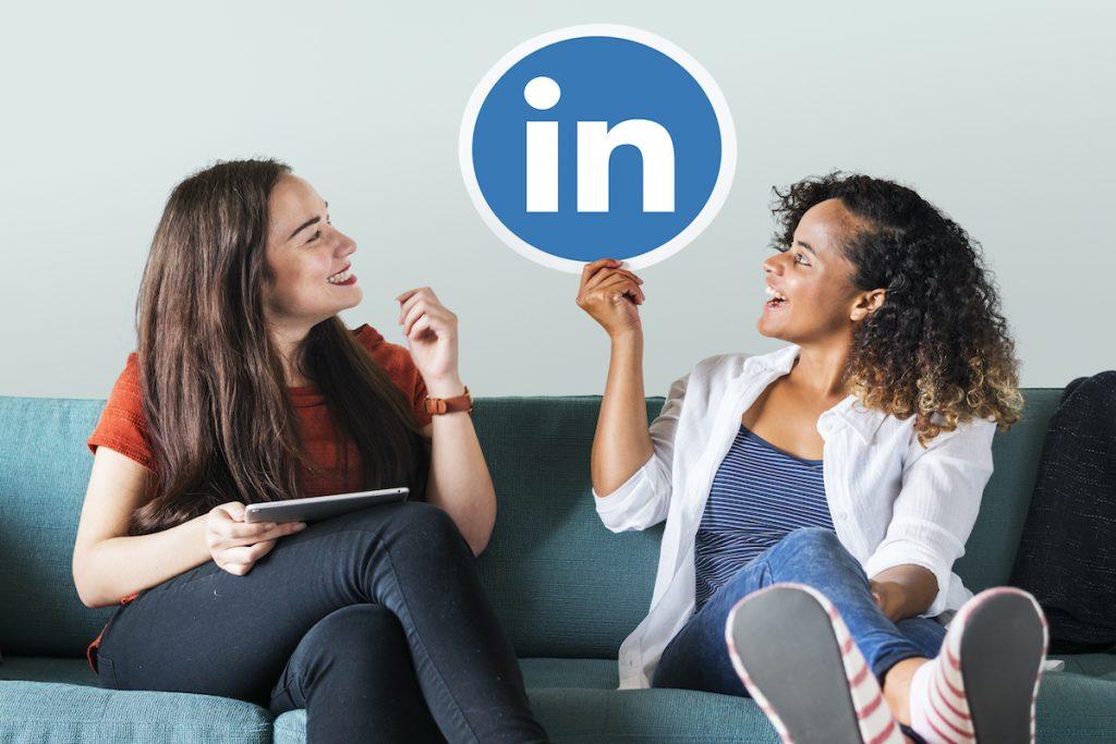 2 mujeres sentadas en un sofá sujetando el logo de linkedin