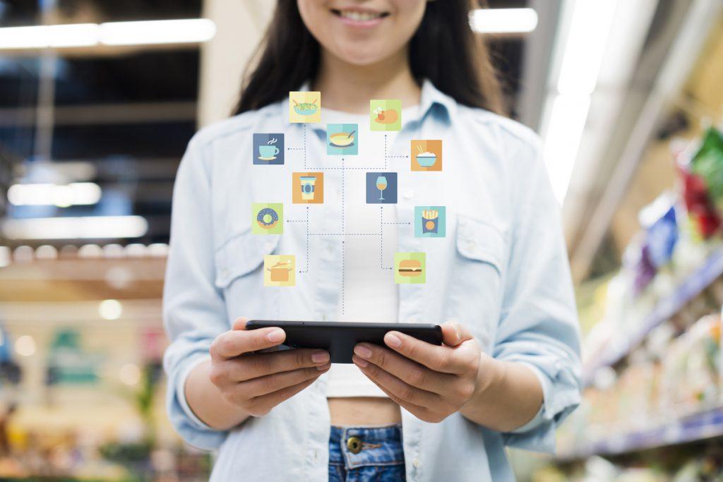 mujer con tablet en la mano de la cual salen aplicaciones
