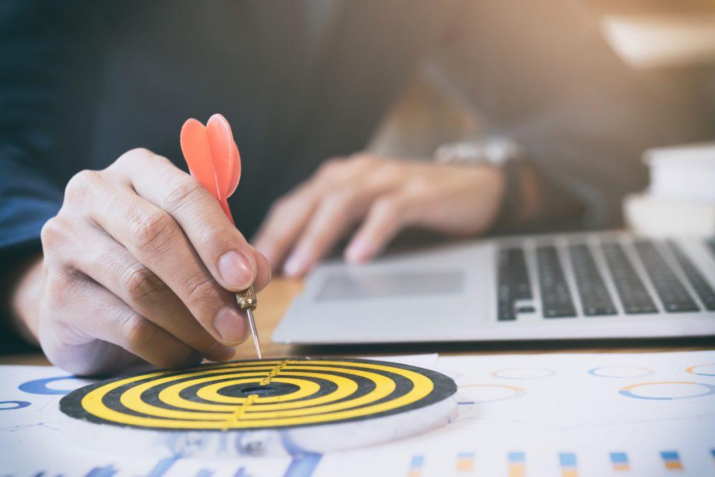 Persona apuntando con un dardo a una diana en su escritorio, junto a un ordenador portátil.