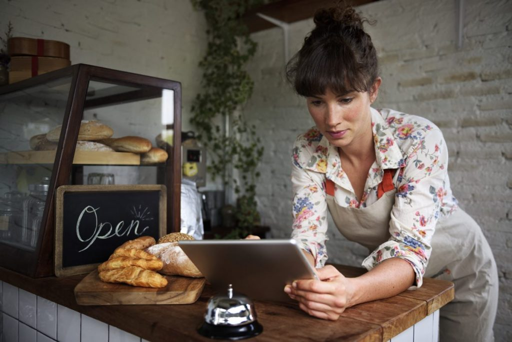 Mujer propietaria de un negocio local utilizando una tablet