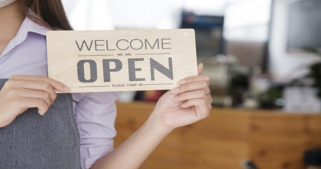 """Mujer con delantal puesto dentro de un restaurante y con un cartel en sus manos que pone """"Welcome we are open"""" en inglés."""