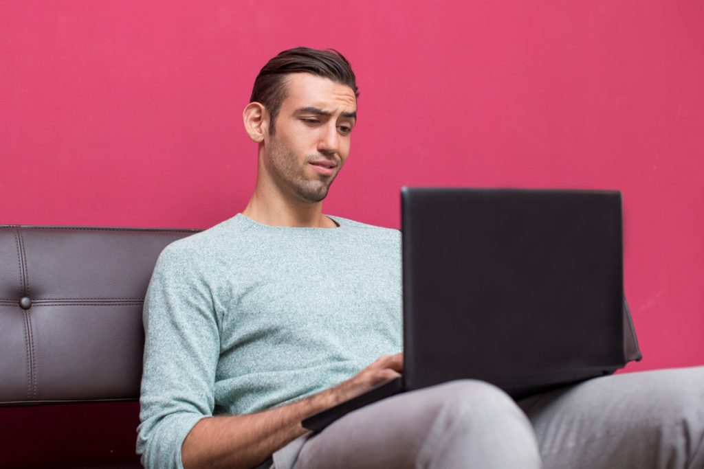 Hombre usando un ordenador portátil mirando la pantalla con desconfianza
