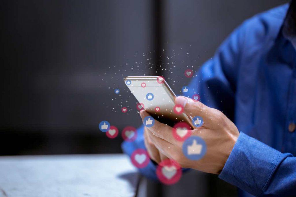 Persona sujetando teléfono móvil mientras recibe notificaciones