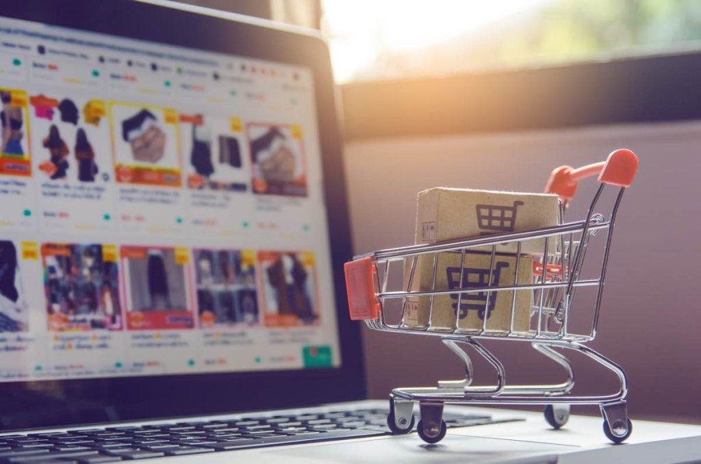 Concepto de venta online. Carrito lleno de cajas. Portátil de fondo