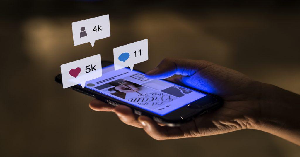 Smartphone sujetado en una mano mostrando varios elementos de interacción de las redes sociales.