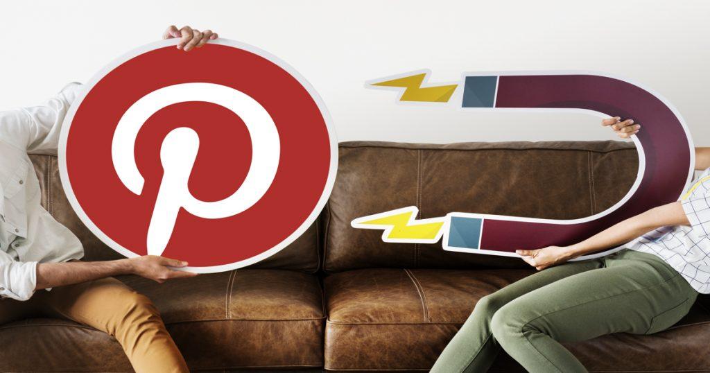 Una persona sujetando el logotipo de Pinterest y otra un símbolo de atracción