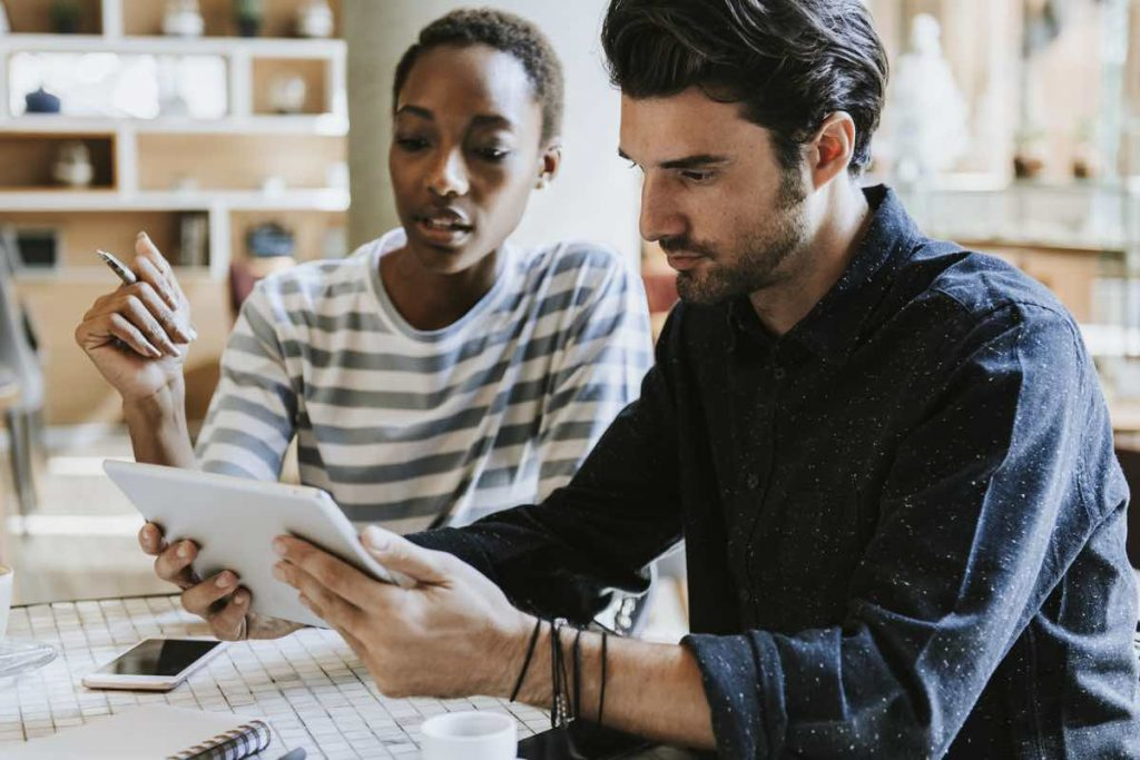 Dos compañeros de marketing revisando los datos de una campaña de publicidad pagada