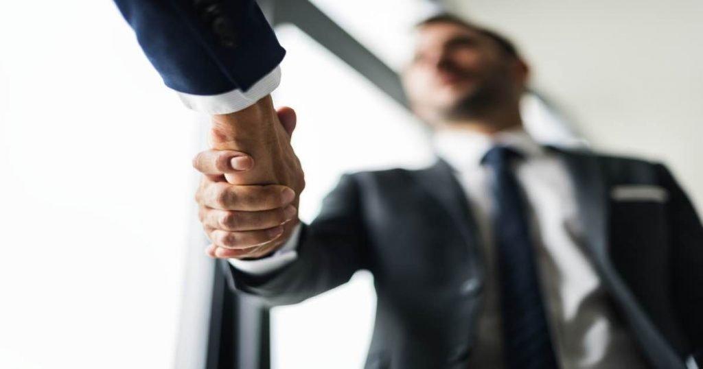 Dos hombres vestidos de traje estrechando sus manos