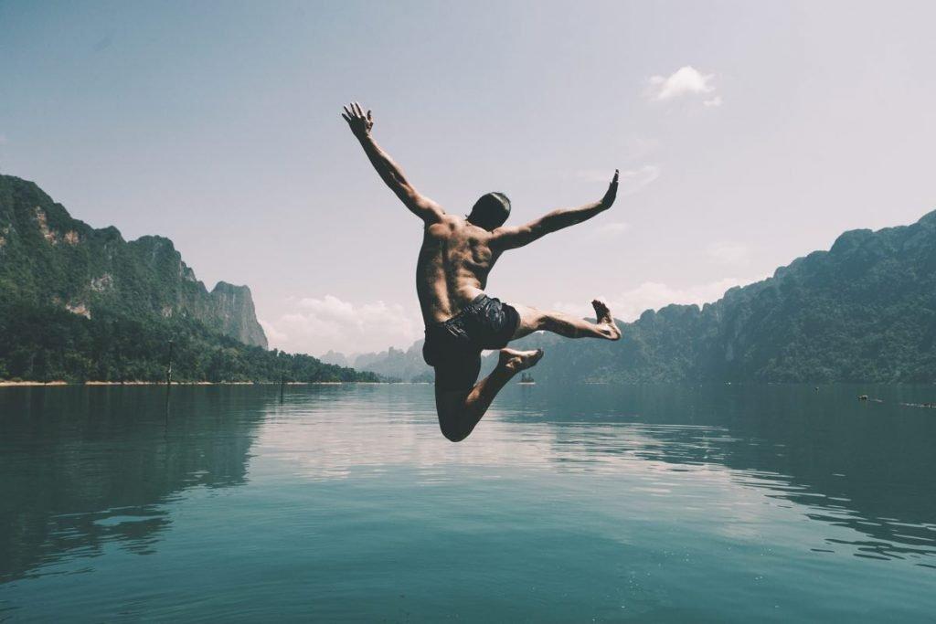 Hombre saltando con alegría a un lago