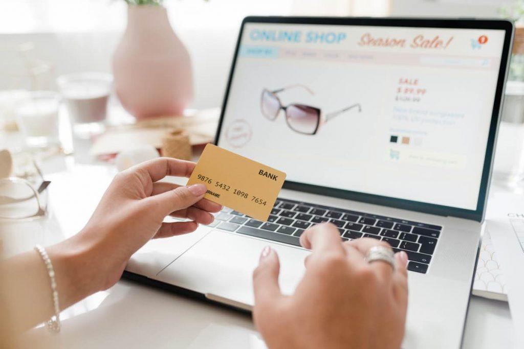 Persona a punto de comprar un producto en una tienda online en su portátil, con una tarjeta de crédito en la mano