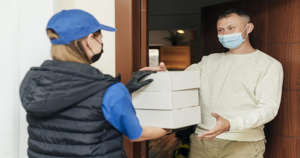 Hombre con mascarilla recibiendo unos paquetes en la puerta de su casa por una repartidora