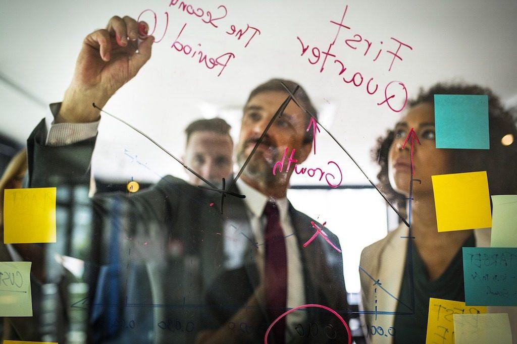 Jefe en oficina con empleados escribiendo en una pizarra