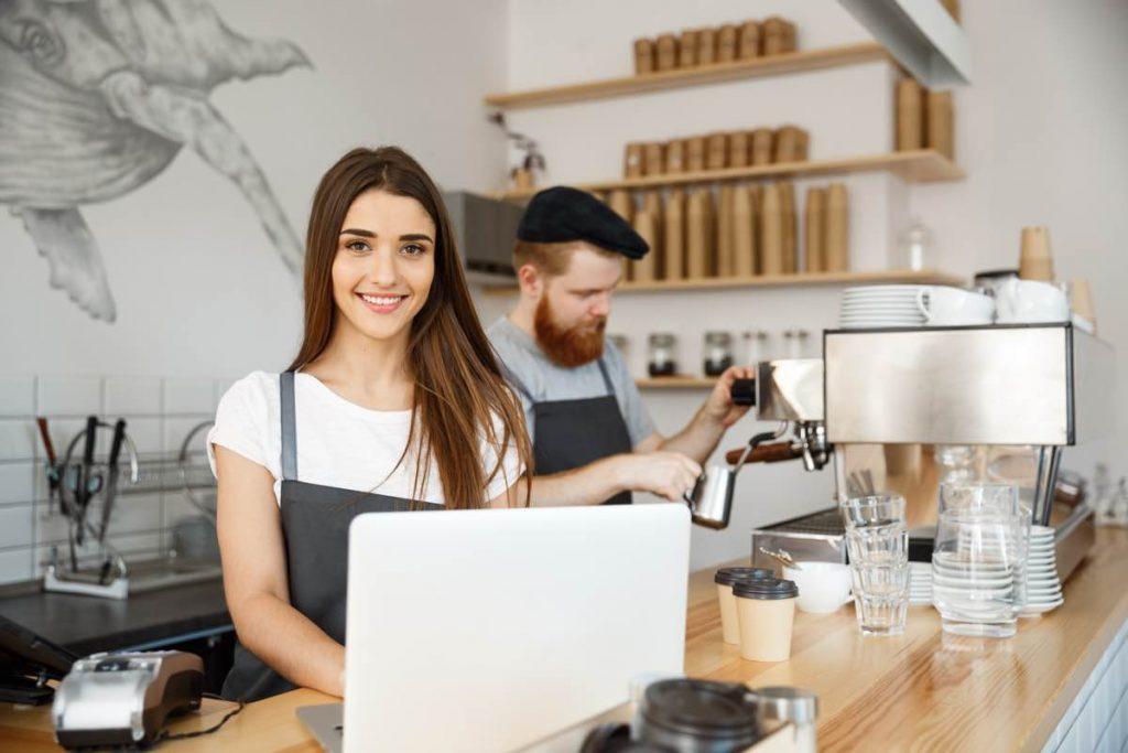 Los propietarios de un bar tras la barra, uno sirviendo una copa y el otro con un ordenador portátil