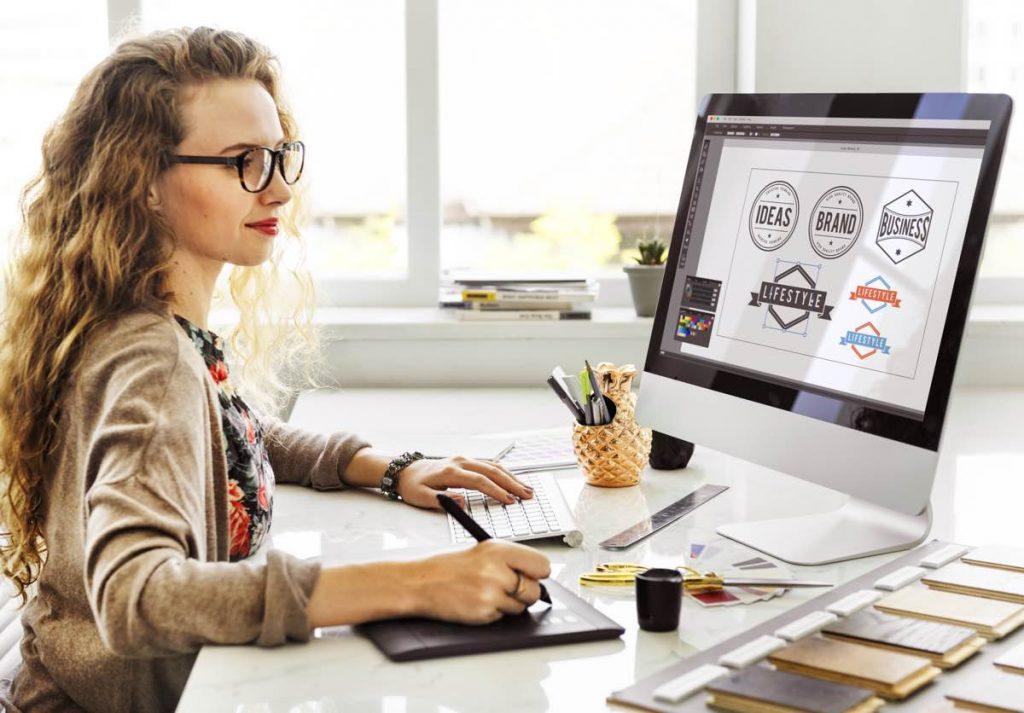 Mujer diseñando logotipo de su marca en un ordenador
