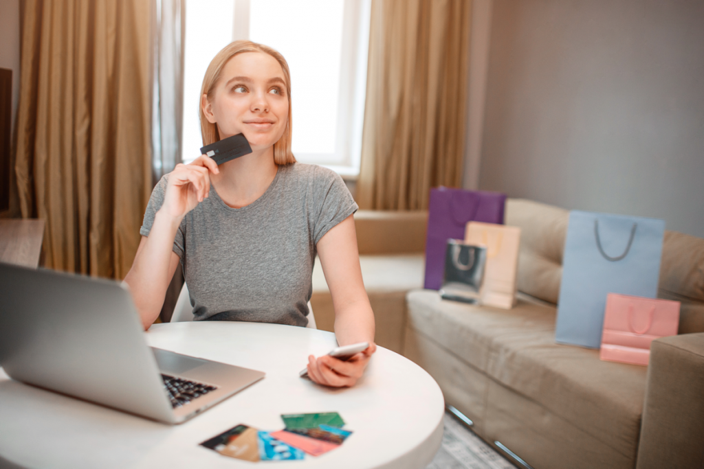 Mujer decidiendo comprar online con visa en la mano