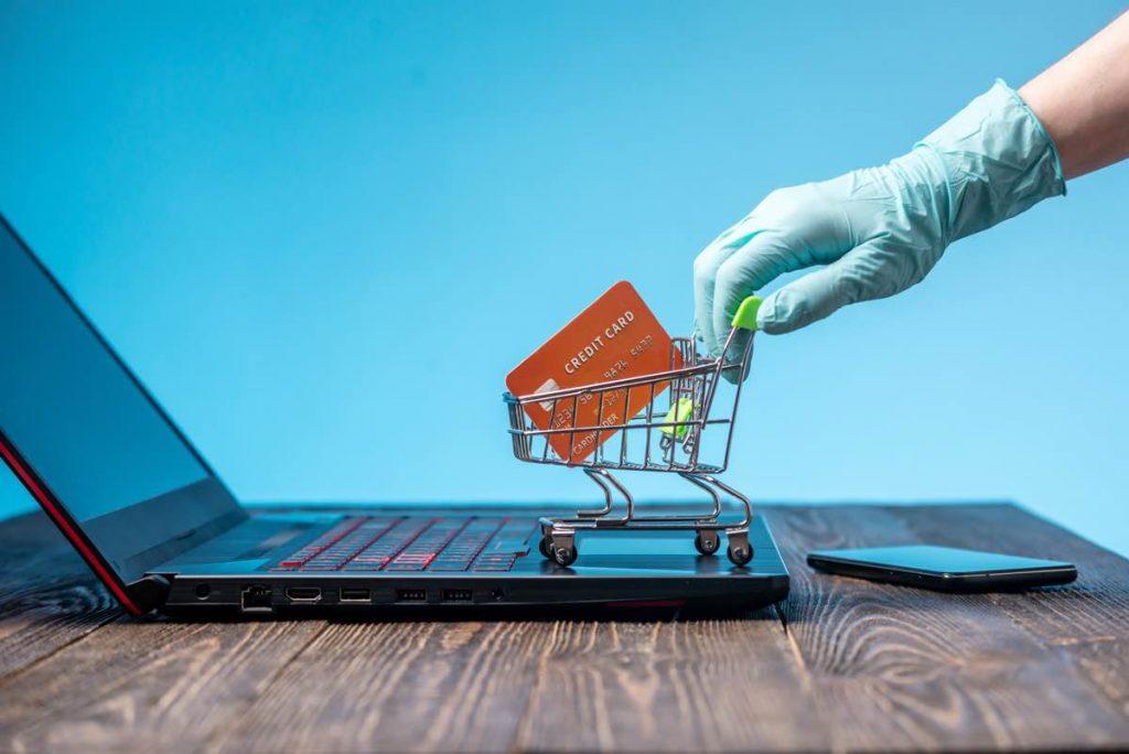 La mano con guante de látex sostiene un carrito de compras con una tarjeta de crédito. Compra por Internet durante la pandemia de coronavirus