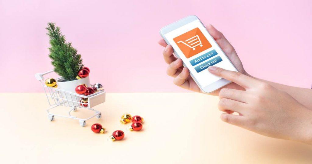 Persona haciendo compra online mediante teléfono móvil durante la Navidad