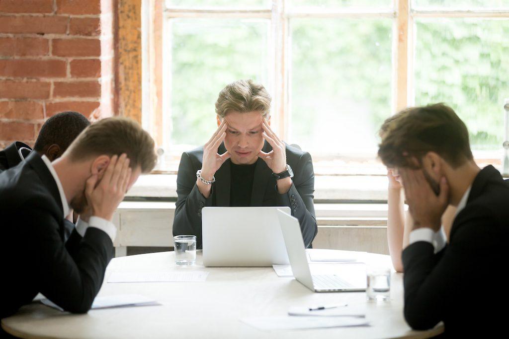 grupo de directivos sentados en una mesa tratando una crisis